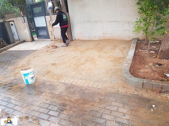 Scattering sand after interlocking flooring